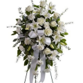 Funeral wreath with construction of white roses with tropical foliage and carnations  - COND 39003