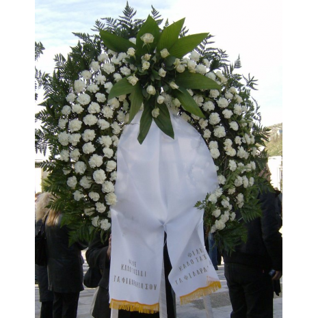 Funeral wreath with construction of white roses with tropical foliage and carnations - COND 39001