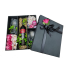 Box with orchids, roses, tropical leaves, wine and glasses